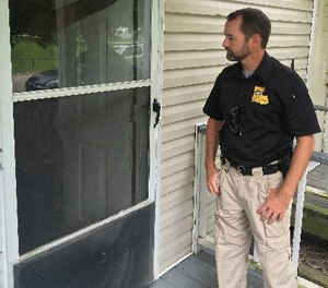 In this photo, an officer checks on one of his cases in Baton Rouge, La. (AP Photo/R.J. Rico)