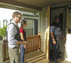 In this May 18, 2017 photo, Milwaukee prosecutor Jeremy Arn, left, Safe & Sound coordinator Claudia Pizano, center, and police officer Chauncey Harris prepare to enter a vacant home on the city's north side after neighbors expressed concern about possible criminal activity. (AP Photo/Ivan Moreno)