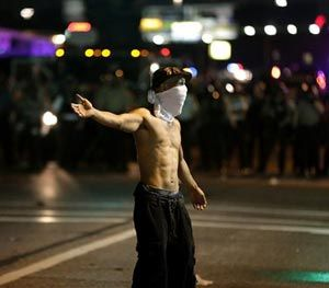A man stands in the street during a protest Monday, Aug. 18, 2014, for Michael Brown, who was killed by a police officer Aug. 9 in Ferguson, Mo. (AP Image)