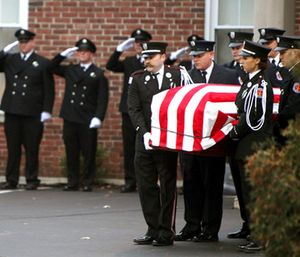 Firefighters move the casket for Patrick Wolterman into an awaiting fire engine at the Hodapp Funeral Home in Cincinnati. (Cameron Knight/The Cincinnati Enquirer via AP)