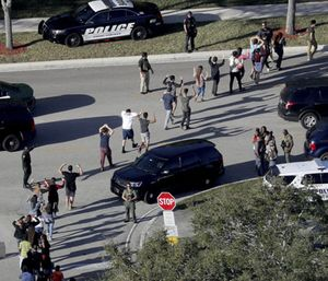 Students hold their hands in the air as they are evacuated by police from Marjory Stoneman Douglas High School in Parkland, Fla. (Mike Stocker/South Florida Sun-Sentinel via AP)