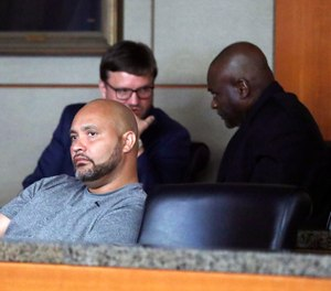 Former Houston police officers Steven Bryant, foreground, and Gerald Goines, background, turn themselves in at the Civil Courthouse, Friday, August 23, 2019, in Houston. (Karen Warren/Houston Chronicle via AP