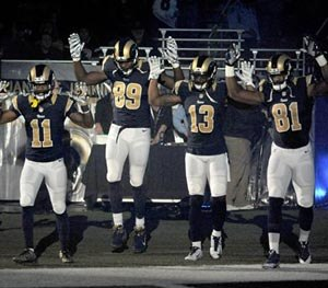Members of the St. Louis Rams raise their arms in awareness of the events in Ferguson, Mo., as they walk onto the field during introductions before an NFL football game against the Oakland Raiders, Sunday, Nov. 30, 2014, in St. Louis. (AP Image)