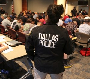 Potential police recruits take a test during an applicant processing event at police headquarters in Dallas, Thursday, Sept. 7, 2017. (AP Photo/LM Otero)