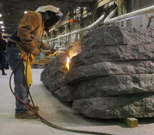 In this Tuesday, Jan. 8, 2019 photo, a worker uses a torch to finish a granite monolith at Rock of Ages in Barre, Vt. The monolith will be one of six that will be part of a permanent dedication to ground zero rescue and recovery workers expected to be unveiled in late May at the National September 11 Memorial & Museum in New York. (AP Photo/Lisa Rathke)