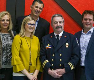 From left, Maureen Bower, daughter Erin Bower Patterson, her father Kevin Bower, Carmel firefighter John Moriarty and Erin's husband Nate Patterson pose for a photo at Moriarty's retirement party. (Jenna Watson/The Indianapolis Star via AP)