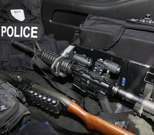 An AR-15 rifle, a shotgun, a vest and other safety gear is pictured in a police patrol car in Edmond, Okla., Thursday, July 14, 2016. (AP Photo/Sue Ogrocki)