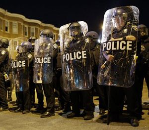 In this April 28, 2015 file photo, police stand in formation as a curfew approaches in Baltimore. (AP Image)