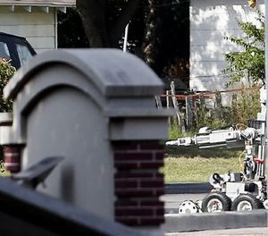 A bomb disposal robot inspects the area surrounding a armored van, top left of frame, during a stand off with a gunman barricaded inside the van, Saturday, June 13, 2015, in Hutchins, Texas. (AP Photo/Brandon Wade)