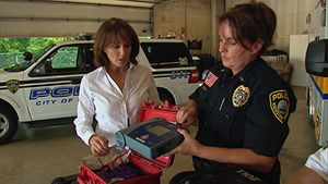 A Rochester Police Officer shows a reporter one of the department''s AEDs (Image/NBC news)