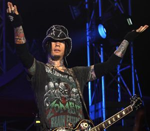 In this Dec. 7, 2012 file photo, Guns N' Roses guitarist DJ Ashba reacts to the crowd as he performs during a concert in Bangalore, India. (AP Image)