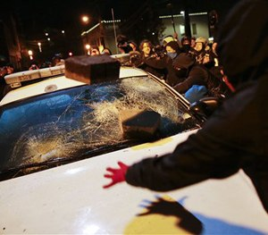 Protesters vandalize a police vehicle outside of the Ferguson city hall in Tuesday, Nov. 25, 2014, in Ferguson, Mo. (AP Image)