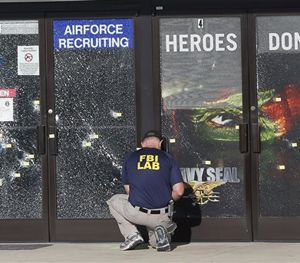 An FBI investigator investigates the scene of a shooting outside a military recruiting center on Friday, July 17, 2015, in Chattanooga, Tenn. (AP Image)