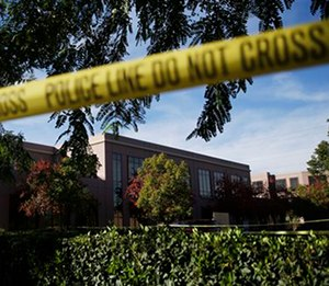 Yellow police tape is strung in front of the Inland Regional Center, site of the mass shooting in San Bernardino, Calif. (AP Photo/Jae C. Hong)