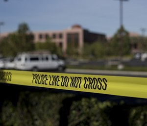Yellow tape is strung around the Inland Regional Center, the site of a shooting rampage that killed 14 people Tuesday, Dec. 8, 2015, in San Bernardino, Calif. (AP Photo/Jae C. Hong)