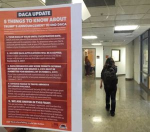 In this photo taken Sept. 7, 2017, a student walks past a tip sheet for Deferred Action for Childhood Arrivals recipients who fear deportation that is taped to a window on the University of California, Berkeley campus in Berkeley, Calif. (AP Photo/Jocelyn Gecker)