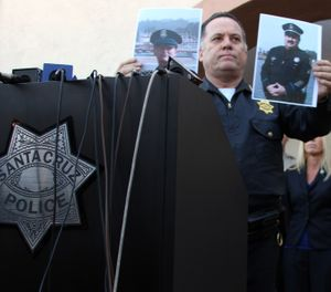 "Santa Cruz Police Chief Kevin Vogel holds up photographs of slain detectives Loran ""Butch"" Baker, right, and Elizabeth Butler on Wednesday, Feb. 27, 2013 in Santa Cruz, Calif. (AP Photo/Thomas Mendoza)"