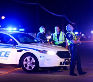 Authorities direct traffic on Hoffmeyer Road near the Vintage Place neighborhood where several law enforcement officers were shot, one fatally, Wednesday, Oct. 3, 2018, in Florence, S.C. (AP Photo/Sean Rayford)