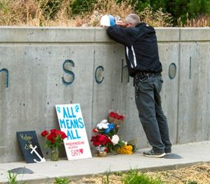 """Freeman High School assistant football coach Tim Smetana shows his grief, Sept. 14, 2017, after he placed roses at a memorial to the shooting victims at the school. """"This is home"""" said Smetana. (Dan Pelle /The Spokesman-Review via AP)"""