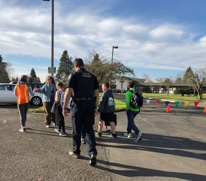 Eugene police officers and teachers escort students at Cascade Middle School in Eugene, Ore., Friday, Jan. 11, 2019. (AP Photo/Andrew Selsky)