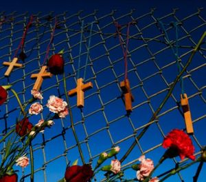Crosses and flowers hang on a fence near Marjory Stoneman Douglas in Parkland, Fla., on Saturday, Feb. 16, 2018, in memory of the 17 people killed in a school shooting on Wednesday. (AP Photo/Brynn Anderson)