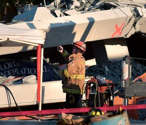 A Miami-Dade Fire Rescue firefighter takes pictures after a brand new, 950-ton pedestrian bridge collapsed in front of Florida International University. (Michael Laughlin/South Florida Sun-Sentinel via AP)