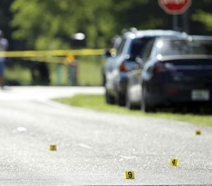 Evidence markers are placed on the street at the scene of a deadly shooting outside of the Club Blu nightclub, Monday, July 25, 2016, in Fort Myers, Fla. (AP Image)