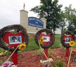 A makeshift memorial is seen before a candlelight vigil in the parking lot the Sikh Temple of Wisconsin Monday, Aug. 5, 2013, in Oak Creek, Wis. Monday is the one-year anniversary of the shooting rampage when a white supremacist at the temple where six people were killed. (AP Photo/Morry Gash)