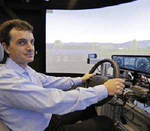 Technical director Dragos Maciuca poses while sitting in a driving simulator in the immersion lab of the Ford Motor Company Research and Innovation Center in Palo Alto, Calif. (AP Photo/Eric Risberg)