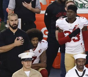 In this Thursday, Sept. 1, 2016 file photo, San Francisco 49ers quarterback Colin Kaepernick, middle, kneels during the national anthem before the team's NFL preseason football game against the San Diego Chargers, in San Diego. (AP Photo/Chris Carlson, File)