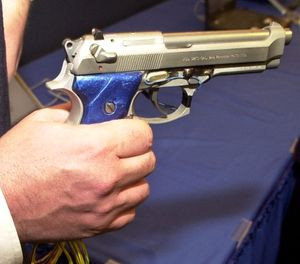 "Michael Recce, associate professor of information systems at New Jersey Institute of Technology and inventor of a ""smart gun"" technology holds a prototype of the gun with grip recognition technology, during a news conference in Newark, N.J., Tuesday, Jan. 6, 2004. (AP Photo/Mike Derer)"