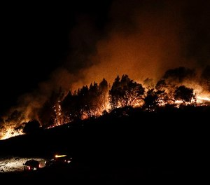 Firefighters watch from their fire trucks as wildfires continue to burn Thursday, Oct. 12, 2017, near Calistoga, Calif. (AP Photo/Jae C. Hong)