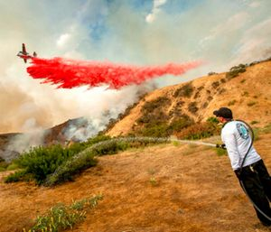 Aaron Funk waters down the hillside behind his parents' home as a plane makes a drop in Sun Valley. (Photo/AP)