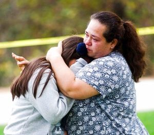 Maria Ortiz consoles her 5th-grade daughter, Crystal Godinez, after she was released from evacuation at Castle View Elementary School in Riverside, Calif., on Tuesday, Oct. 31, 2017. (Watchara Phomicinda/The Press-Enterprise via AP)