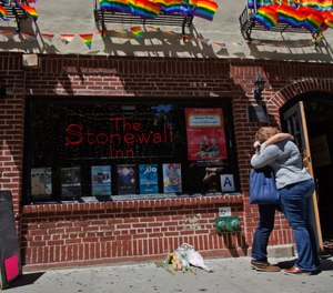 A couple embraces outside the Stonewall Inn in New York (AP Photo/Mary Altaffer, File)