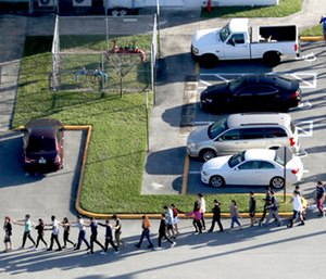 Students are evacuated by police from Marjory Stoneman Douglas High School in Parkland, Fla. (Mike Stocker/South Florida Sun-Sentinel via AP)