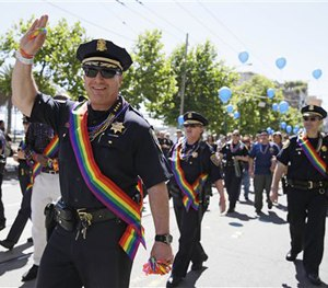 SF Police Chief Greg Suhr waves while marching with a number of his cops in the 44th annual Gay Pride parade Sunday, June 29, 2014. (AP Image)