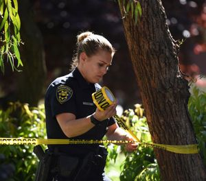 Sunnyvale Public Safety Officer Kira Reid secures the perimeter at the apartment complex believed to be associated with a car crash suspect in Sunnyvale, Calif., on Wednesday, April 24, 2019. (AP Photo/Cody Glenn)