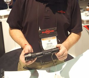 Surefire employee Kevin McCluskey holds up the newest version of the R1 Lawman rechargeable flashlight, which now includes IntelliBeam. (Image/PoliceOne)