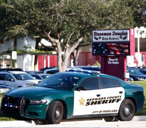 In an Aug. 15, 2018 file photo, a Broward County Sheriff's Office vehicle is parked outside Marjory Stoneman Douglas High School, in Parkland, Fla. (AP Photo/Wilfredo Lee, File)
