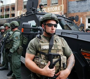 Members of a SWAT team keep an eye on demonstrators in Charlottesville, Va., Sunday, Aug. 12, 2018. (AP Photo/Steve Helber)