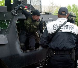 Whitman County Sheriff Deputy Chris Chapman climbs out of the Whitman County Washington Regional SWAT Team armored vehicle outside the Moscow Police Department in Moscow, Idaho, Sunday, May 20, 2007. (AP Image)