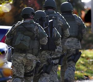 SWAT move in a line on the campus of Central Connecticut State University, Monday, Nov. 4, 2013, in New Britain, Conn. (AP Photo/Jessica Hill)