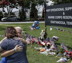 Two embrace in front of a makeshift memorial at the Navy Operational Support Center and Marine Corps Reserve Center, Saturday, July 18, 2015, for the victims of the July 16 shootings in Chattanooga, Tenn.