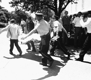 In this Aug. 1, 1966, file photo, one of the victims of Charles Whitman, the sniper who gunned down victims from a perch in the University of Texas tower, is carried across the campus to a waiting ambulance in Austin. (AP Photo/File)