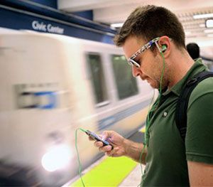 Nick Sabatasso checks his cell phone while waiting for a BART train at San Francisco's Civic Center station. (AP Image)