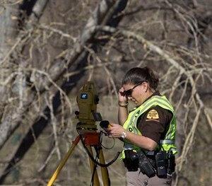 In this March 7, 2015 photo, officials respond to a report of car in the Spanish Fork River in Spanish Fork, Utah. (AP Image)