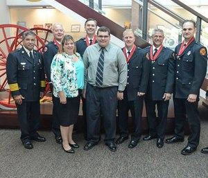 Toledo firefighters pose with Michael Rheinbolt, who they rescued last year, and his mother. (Photo/ Toledo Fire & Rescue)