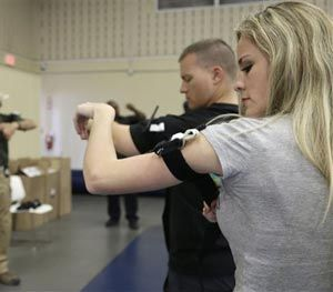 In this June 3, 2014 photo, Houston police officer Austin Huckabee, left, demonstrates how to apply a tourniquet to officers Angeline Cotter, right, and Thomas Emmite, Jr. at the police academy in Houston. (AP Image)