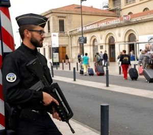 A police officer stands guard while passengers enter the Marseille Saint Charles train station, a day after a man fatally stabbed two women outside the train station, in Marseille, southern France, Monday, Oct. 2, 2017. (AP Photo/Claude Paris)